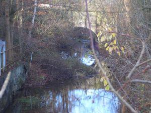 Die Tonnenbrücke am Untergraben, dahinter die früheren 6 Reinigungsreiche (Klärteiche, heute Schrottverwertung).